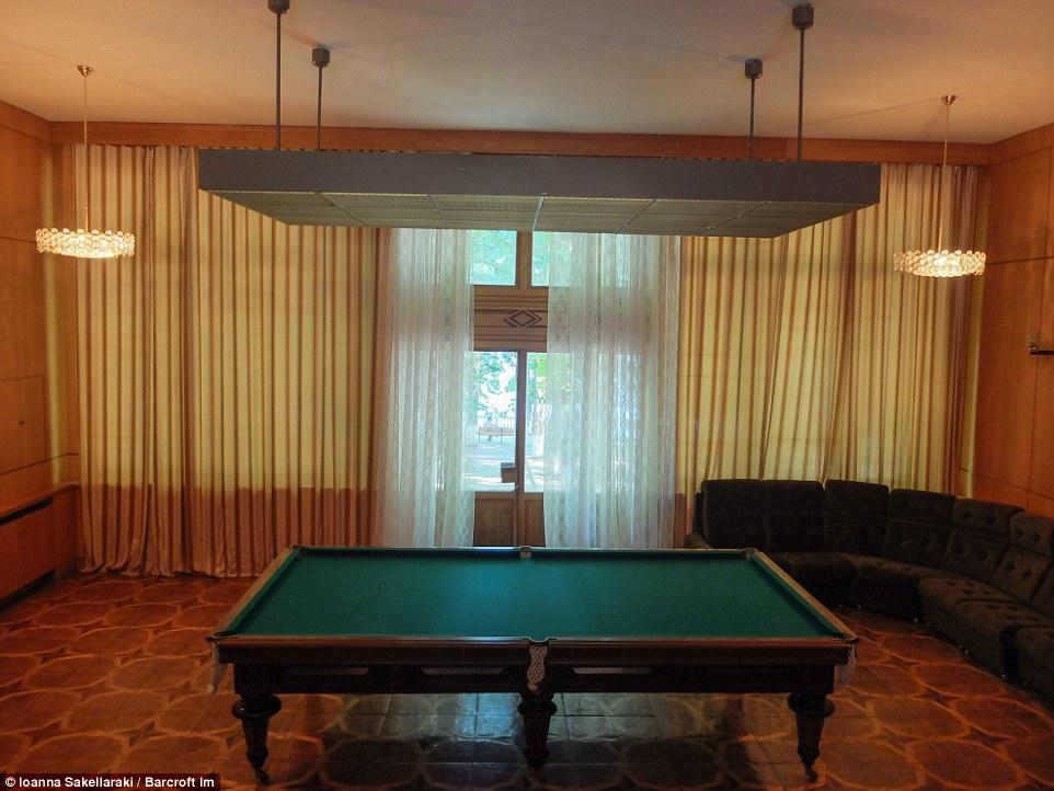 Игровая комната с деревянным бильярдным столом, окнами от потолка до пола и огромным диваном.