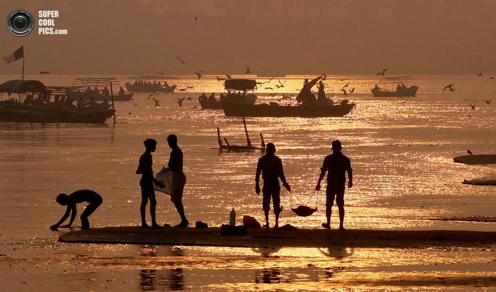 Индийские рабочие собирают мусор на берегу реки в преддверии праздника.(Sanjay Kanojia/AFP/Gett