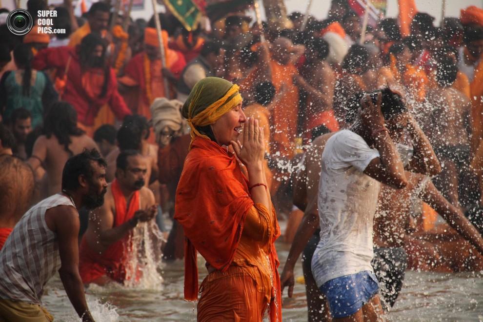 Женщина молится под брызгами воды. (AP Photo/Deepak Sharma)