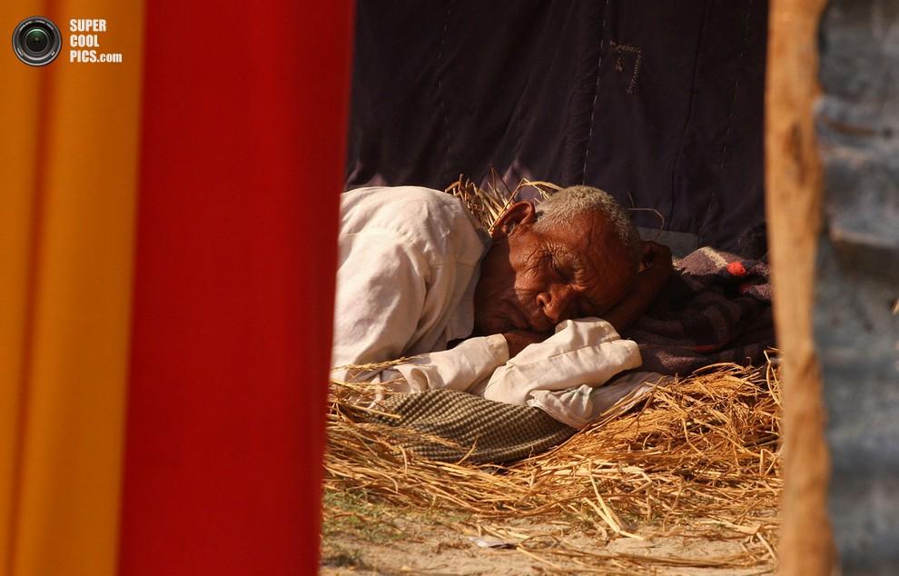Индийский мужчина отдыхает на ложе из соломы.(Sanjay Kanojia/AFP/Getty Images)