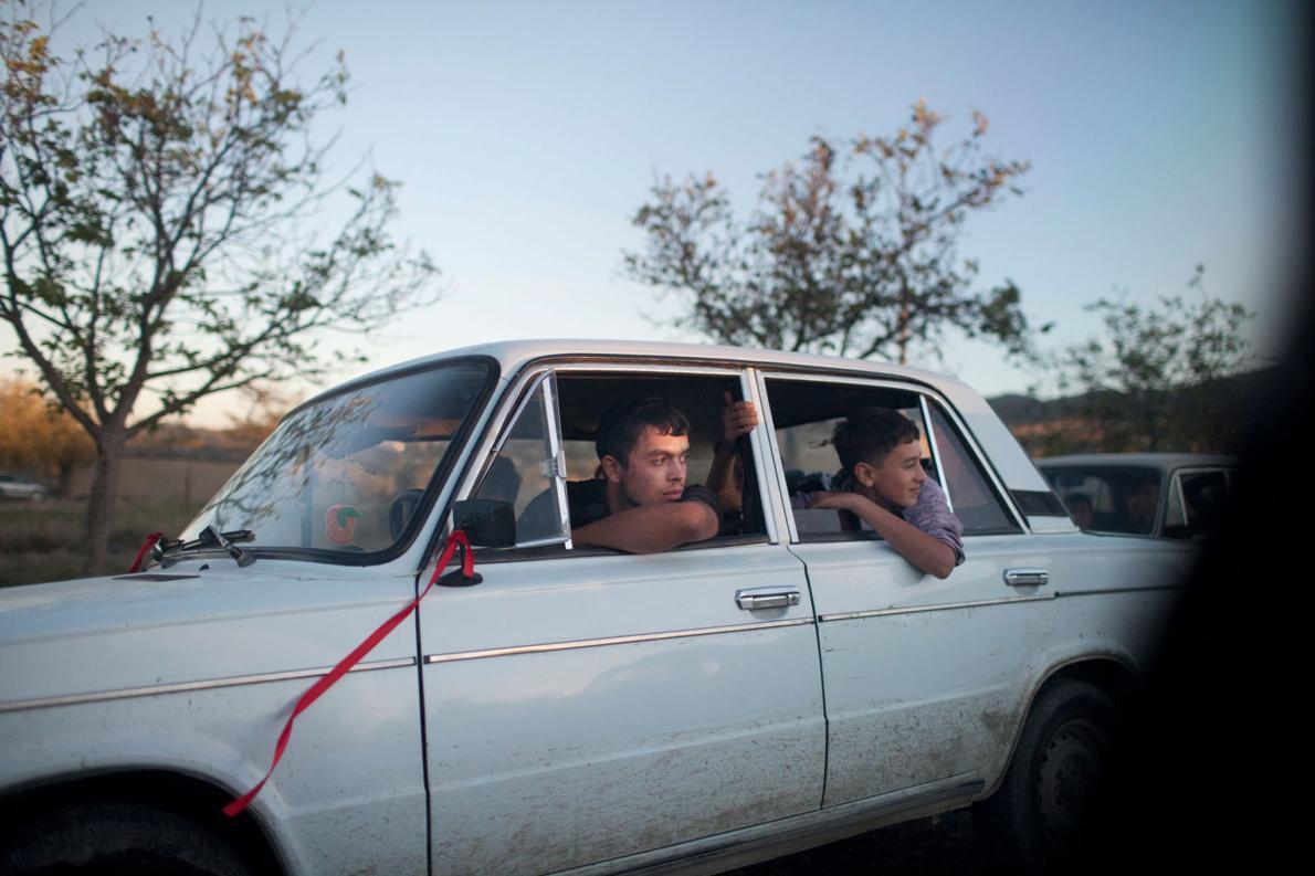 Парни-подростки сморят из окон машины на свадебные торжества. Люди на снимках Сулакаури — грузинские