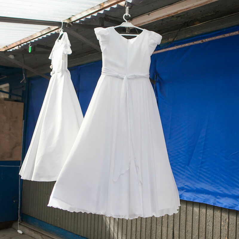 wedding dresses for sale hanging on a street market in Warsaw