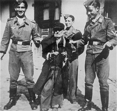Three young Germans publicly humiliate an elderly Jew in the streets of Krzemieniec.jpg
