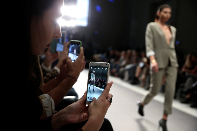 Audience take photos of a model presenting a creation by Greek designer Dimitrios Ordoulidis during