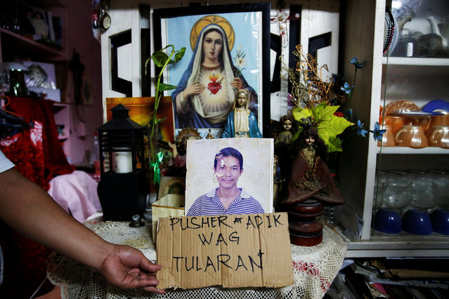 A relative holds a cardboard next to a picture of Florjohn P. Cruz inside a house where he was kille