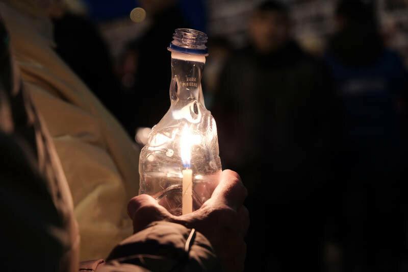 женщина держит в руках свечу в бутылке