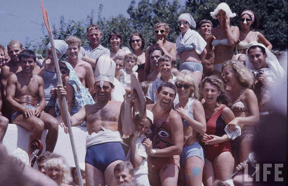 Отдых на пляже. Групповой снимок улыбающейся молодежи для американского фотографа.