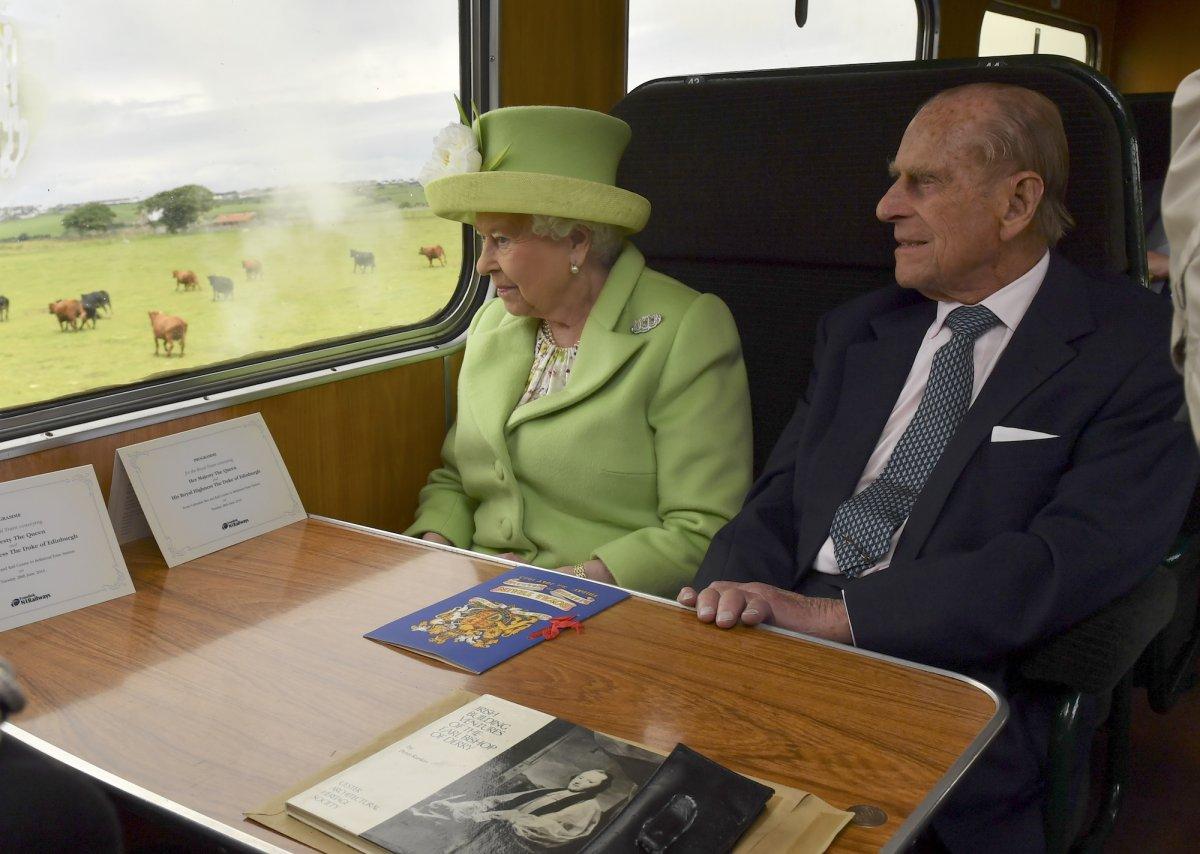 Елизавета II и принц Филипп едут на паровозе мимо города Колрейн, Северная Ирландия.