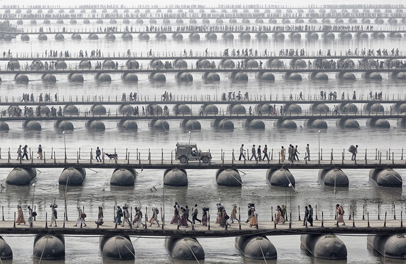 Pilgrims and devotees cross pontoon bridges at the Maha Kumbh Mela - the largest spiritual gathering