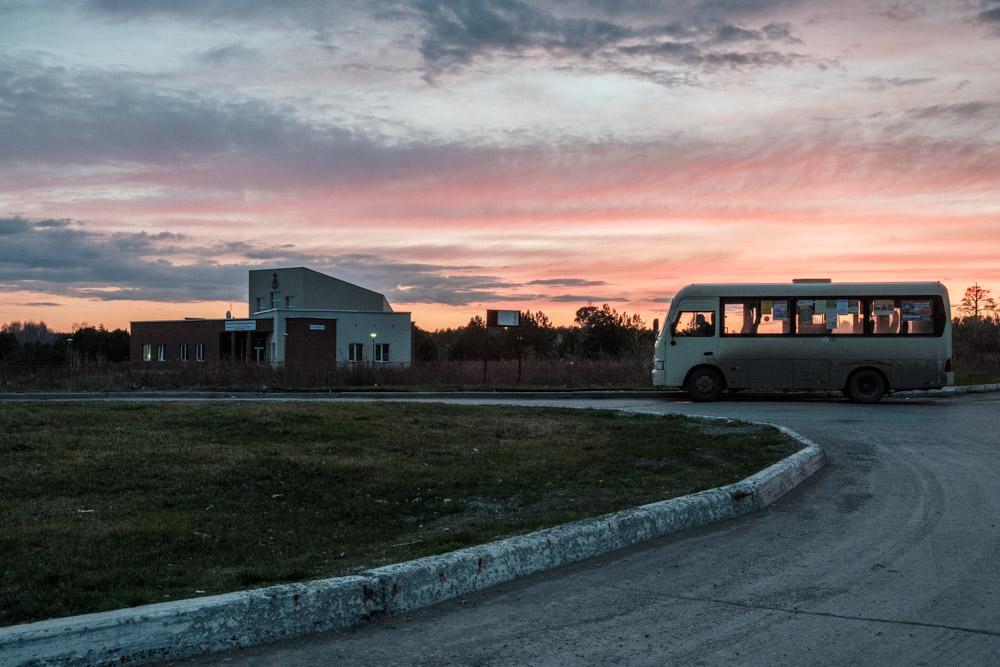 автобус на остановке, фотография снятая на фоне заката