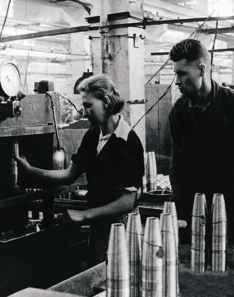 Челябинск. Оборонный завод. Стахановец Н. Д. Голиков помогает в освоении профессии работнице завода. 1942