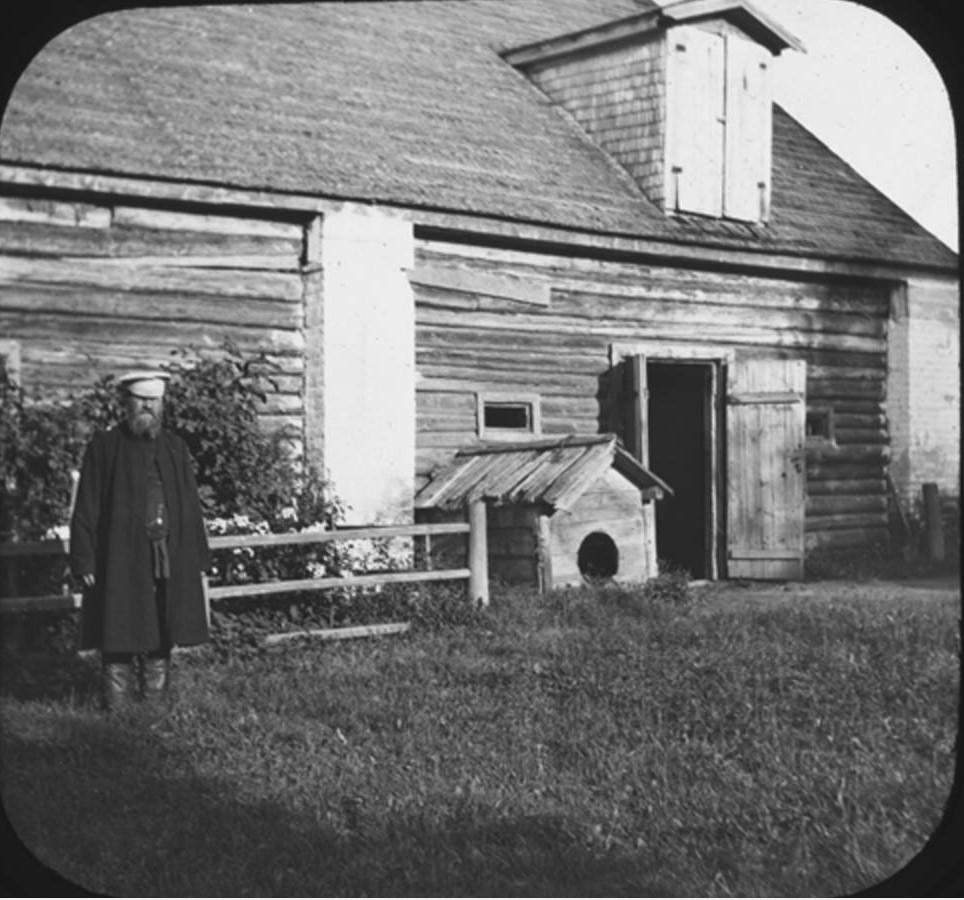 06. Слуга Иван стоит слева от бокового входа в амбар. Рядом со входом — собачья будка