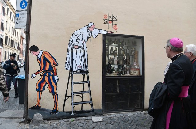 A bishop walks past a new street-art collage by Italian artist Maupal showing Pope Francis playing t