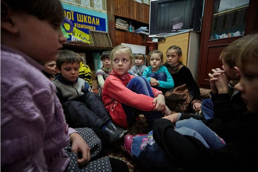 Первоклассники на востоке Украины, среди которых 6-летняя Саша (в красном свитере), участвуют в практических занятиях, посвященных тому, как им действовать в случае обстрелов