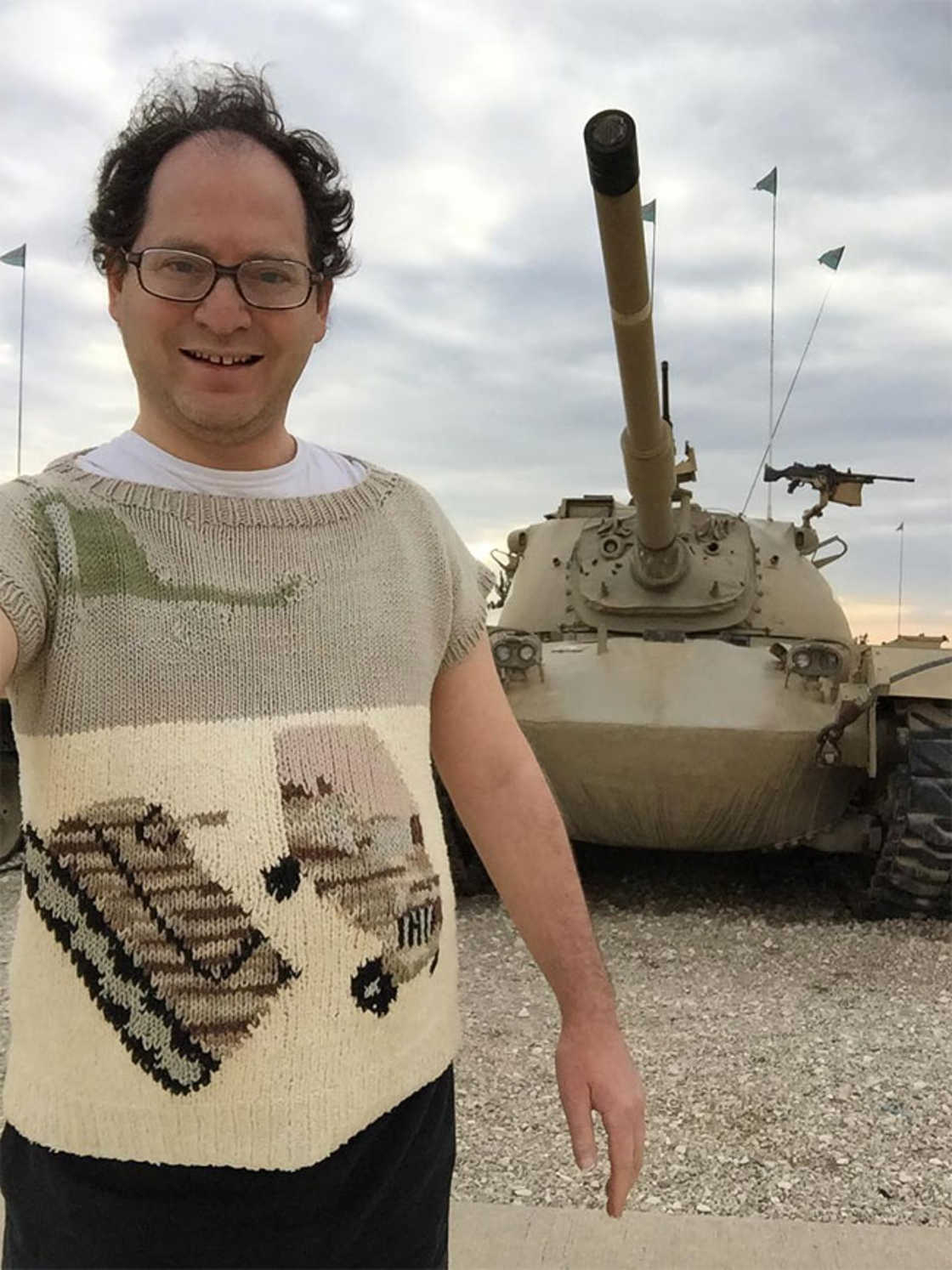 He knits sweaters of the places he visits to take a picture wearing it