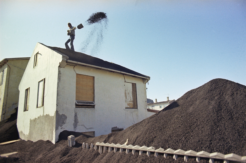 Вестманнаэйяр. Мужчина сбрасывает лопатой пепел с крыши