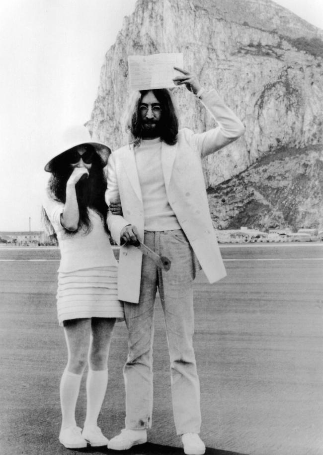 © Eastnews  Джон Леннон показывает свидетельство обраке нафоне Гибралтарской скалы. Леннон и