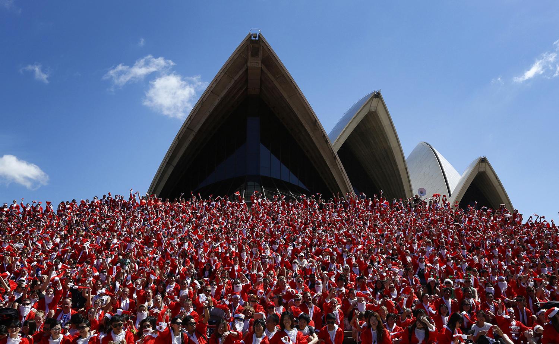 Тысячи участников традиционного группового забега в костюмах Санты, Сидней.