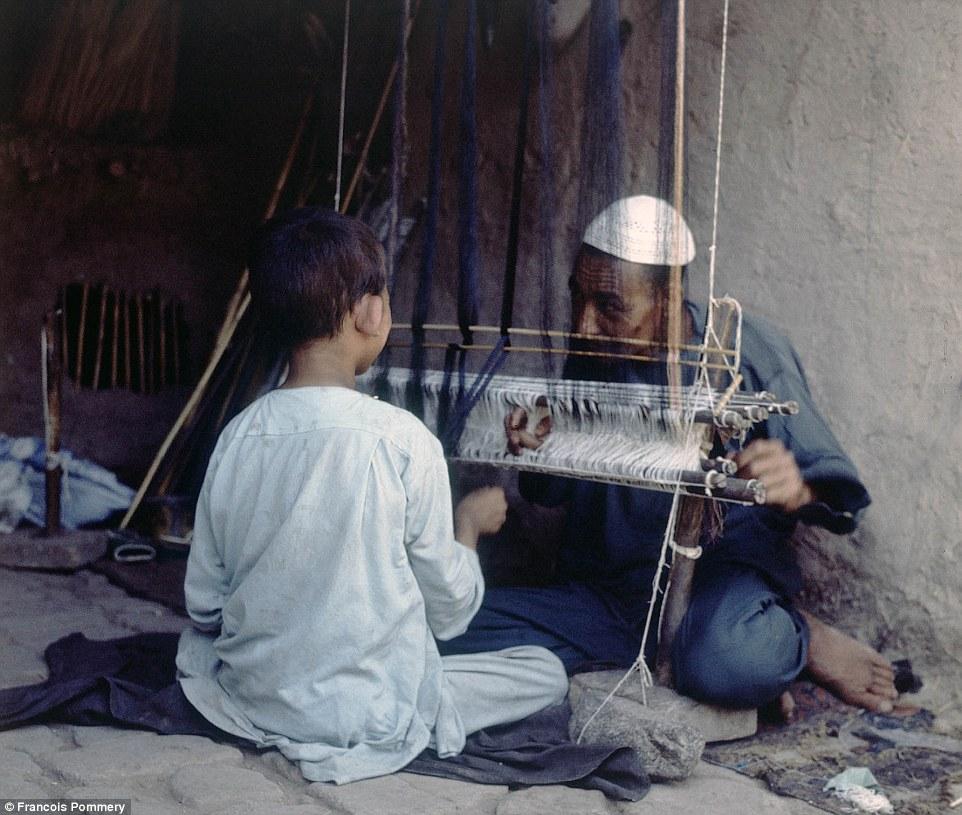 Знания переходят из поколения в поколение: мужчина учит мальчика, как работать на ткацком станке.