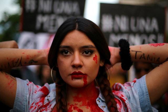 A demonstrator depicting lacerations poses during a peaceful march against gender violence in Santia