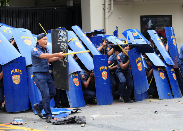 Policemen advance in formation during a violent dispersal of various activist and Indigenous People&