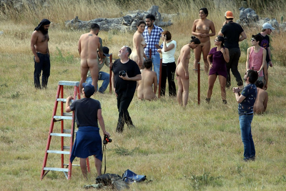 People prepare to pose nude as photographer Spencer Tunick looks to the sky during his art installation