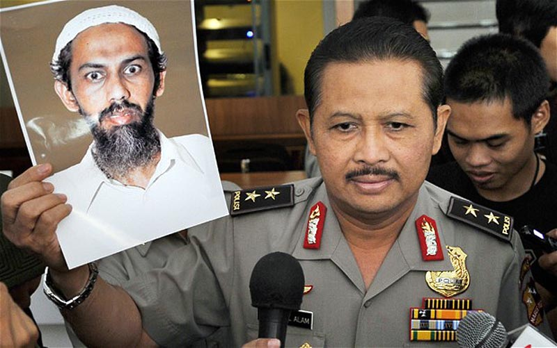 13. Представитель индонезийской полиции держит в руках фотографию Умара Патека, предполагаемого вдох
