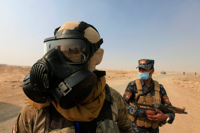 Iraqi forces wear protective masks after winds brought fumes from a nearby sulfur plant set alight b