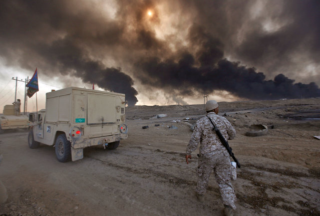 Iraqi army are seen in Qayyara, Iraq, October 22, 2016. The fumes in the background are from oil wel