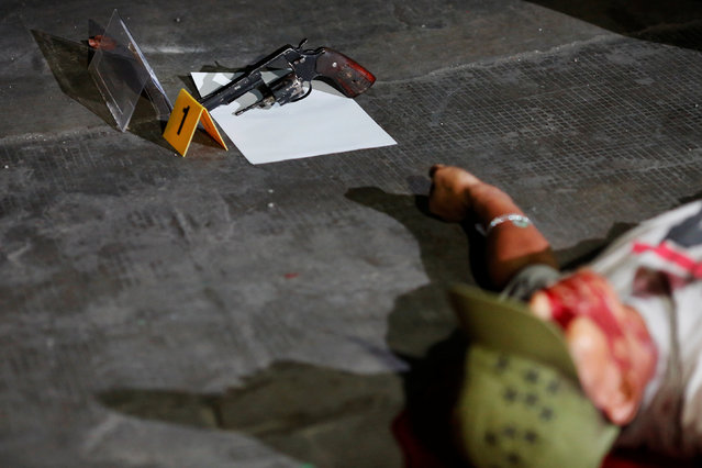 A gun is seen next to the body of a man was killed in a shootout with police in Manila, Philippines