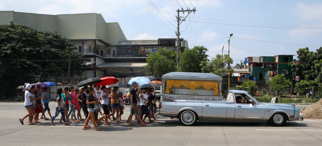 Families and friends walk behind the hearse transporting the coffin of Vicente Batiancila, whom poli
