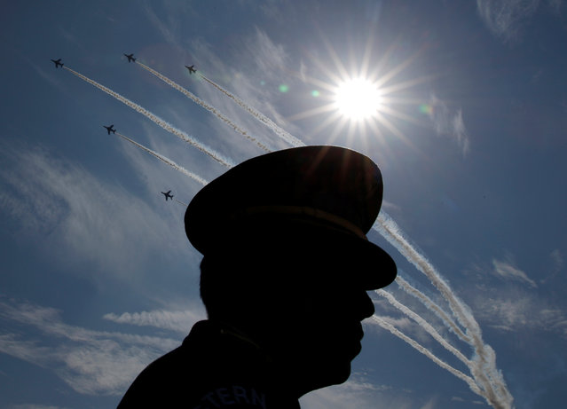 Japanese Self-Defence Forces' (SDF) official is silhouetted while flights performs air show dur