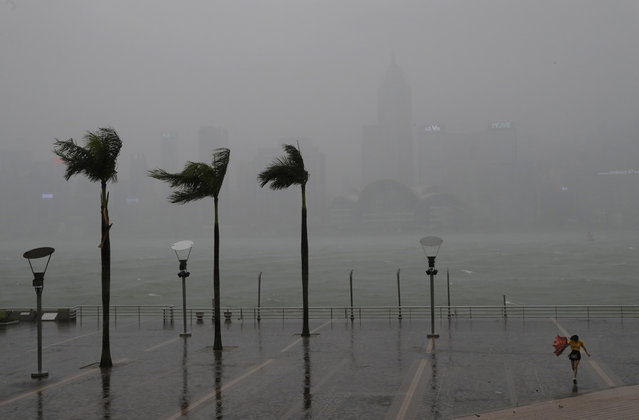 A woman braves the wind on the waterfront of Victoria Habour as Typhoon Haima approaches Hong Kong,