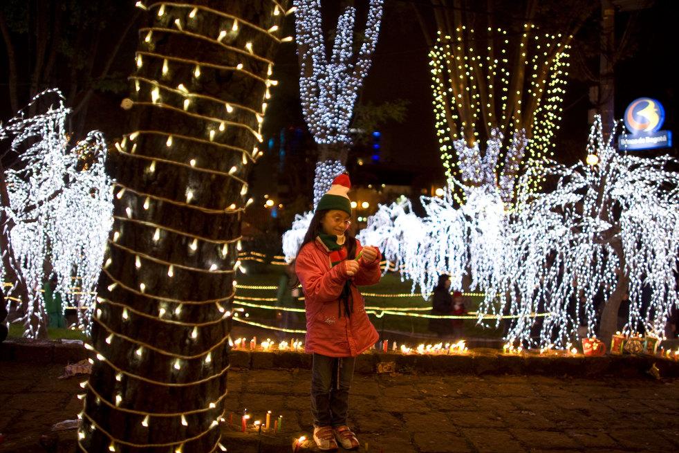 16. Девочка зажигает свечу в вечер свечей в Боготе, Колумбия. Колумбийцы традиционно зажигают свечи