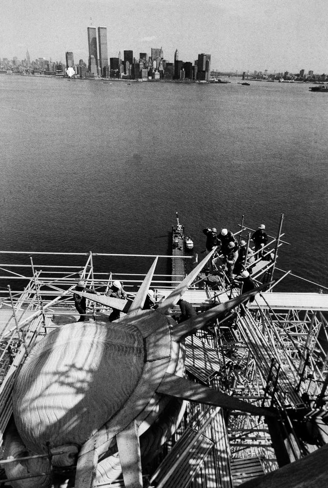49. Рабочие снимают первый из семи шипов короны статуи Свободы во время реставрационных работ, 5 апр