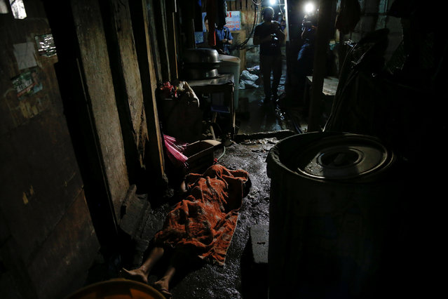 The body of a man killed is covered with a blanket inside a slum in port area of Manila, Philippines