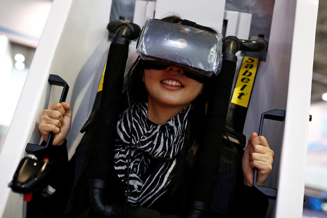 A woman sits in a VR Capsule, a virtual reality simulator, at the WRC 2016 World Robot Conference in