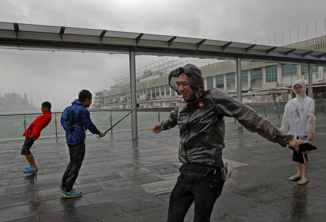 People play with strong wind caused by Typhoon Haima on the waterfront of Victoria Habour in Hong Ko
