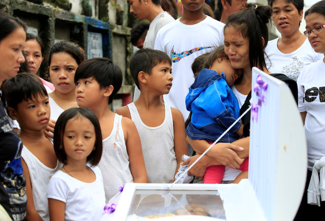 Loved ones and friends gather in front of the coffin to view the body of Apolinario Eyana Jr., who w