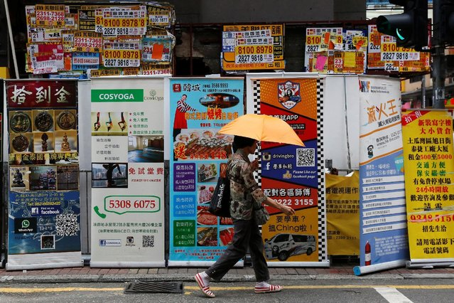 A woman walks past banners promoting retail goods and services displayed in front of closed shops fo
