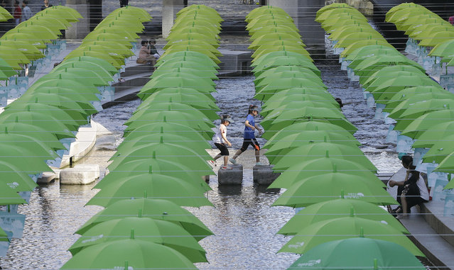 Children walk under umbrellas on display over Cheonggye stream during a campaign to raise donations