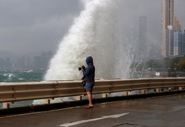A man takes a photo on a waterfront as Typhoon Haima approaches in Hong Kong, China, October 21, 201