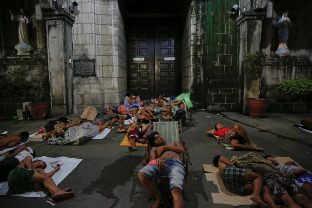 People sleep outside a church in Manila, Philippines early October 18, 2016. People who have been sp
