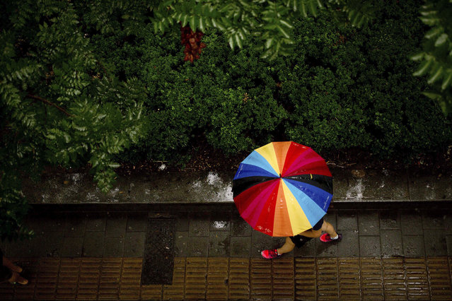 A woman carries a rainbow-colored umbrella as she walks during a rain shower in Beijing, Thursday, A