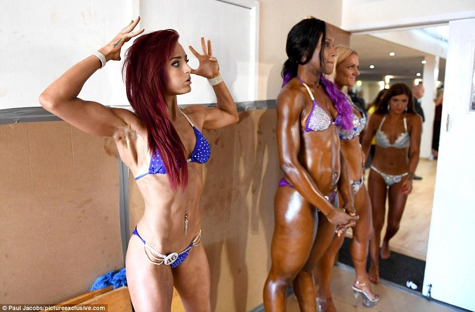 Бодибилдеры заняты последними приготовлениями перед выступлением, нанося на свои мускулы искусственн