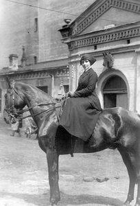 Наездница в амазонке на лошади у конюшни.
