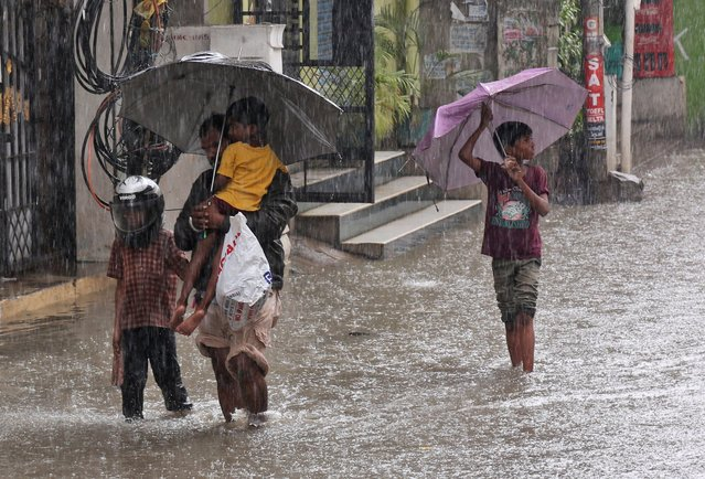 Indians wade through a waterlogged street as it rains in Hyderabad, India, Wednesday, September 21,