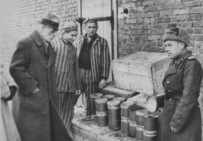 Советский офицер и бывшие узники концлагеря Освенцим II (Биркенау) возле ящиком с контейнерами с отравляющим газом «Циклон-Б»
