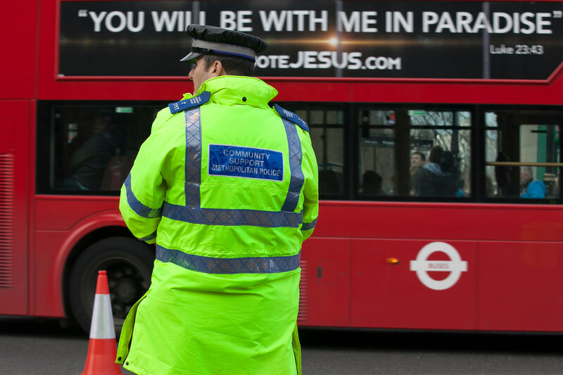 The policeman stands opposite the passing bus, on which the slogan - you will be with me in paradise. After the terrorist attack in London