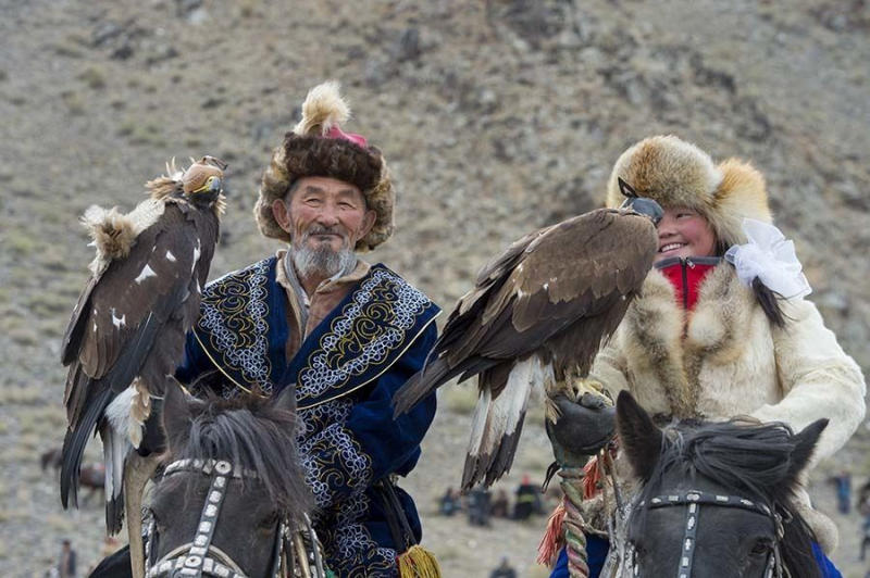 The oldest Kazakh eagle hunter participant and a teenage girl eagle hunter (winner of 2014 competiti